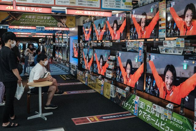TVs display a reaction of Japan's Uta Abe, the gold medallist of the judo women's -52kg during the Tokyo 2020 Olympic Games, to celebrate the victory of her brother Hifumi Abe as he wins the judo men's -66kg final at an electronics retail shop in Tokyo on July 25, 2021. (Photo by Yasuyoshi Chiba/AFP Photo)