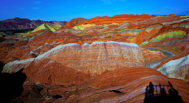 View of colourful rock formations at the Zhangye Danxia Landform Geological Park in Gansu Province, China. The Zhangye Danxia Landform Geological Park is 40km from Zhangye city. The park spans more than 400 square kilometers in Gansu. The unusual terrain is the result of red sandstone and mineral deposits carved over the years by natural forces. A number of boardwalks have been built to encourage visitors to explore the rock formations. (Photo by ImagineChina/The Grosby Group)