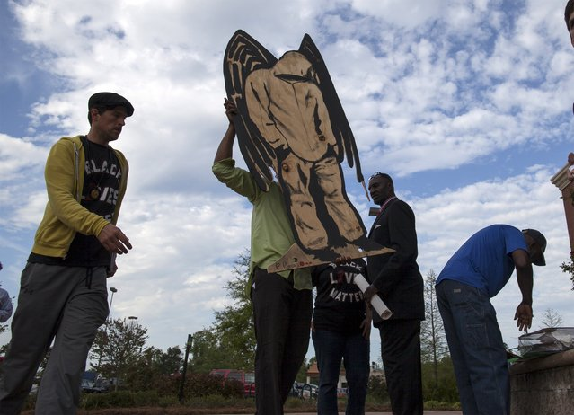 Protesters carry a sign with an image of Trayvon Martin at a rally in North Charleston, South Carolina April 8, 2015. (Photo by Randall Hill/Reuters)