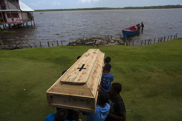 In this September 2, 2018 photo, relatives and friends carry the coffin that contains the remains of Miskito diver Oscar Salomon Charly, 31, to be transported via a boat to a nearby cemetery, in Cabo Gracias a Dios, Nicaragua Charly died in Honduras after suffering a severe case of decompression sickness. (Photo by Rodrigo Abd/AP Photo)