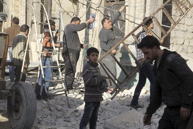 Residents inspect damage and make repairs after an airstrike on the rebel held al-Fardous neighbourhood of Aleppo, Syria February 18, 2016. (Photo by Abdalrhman Ismail/Reuters)