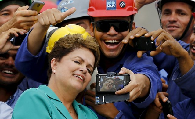 Brazil's President Dilma Rousseff takes a selfie with workers during a visit to the Rio 2016 Olympic Park in Rio de Janeiro in this September 30, 2014 file photo. (Photo by Ricardo Moraes/Reuters)