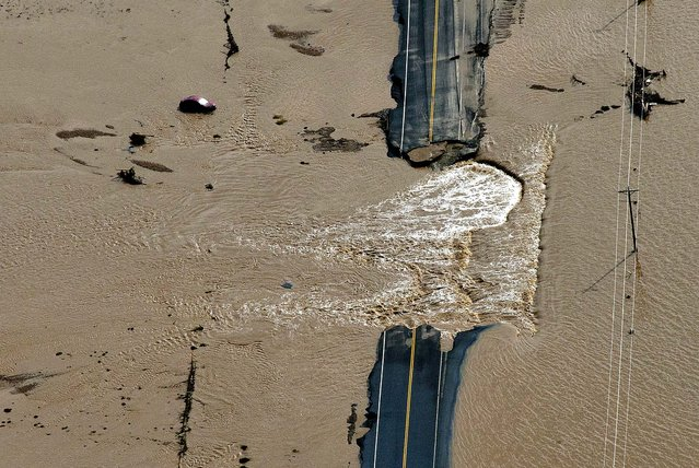 A section of highway is washed out by flooding along the South Platte River in Weld County, Colorado near Greeley, Saturday, September 14, 2013. (Photo by John Wark/AP Photo)