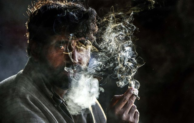 A stranded passenger smokes as he waits for the Jammu-Srinagar highway to reopen at a bus station in Jammu, India, on January 2, 2013. Heavy snowfall along the highway connecting the Kashmir valley with the rest of the country, remained closed for the third consecutive day. (Photo by Channi Anand/Associated Press)
