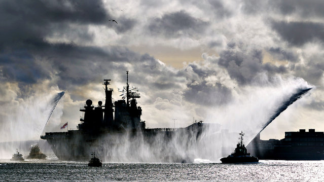 Fire tugs spray jets of water into the air as HMS Illustrious returns to Portsmouth Royal Navy Base almost a month later than planned after being diverted to the Philippines following Typhoon Haiyan, on January 10, 2013. The 23,000-tonne helicopter carrier was operating in the Gulf, in November, expecting to be home on December 13th. (Photo by Chris Ison/PA Wire)
