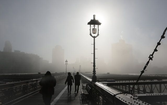 Fog mutes the Brooklyn skyline as it rolls onto the Brooklyn Bridge on Wednesday, January 15, 2014, in New York. Fog challenged morning travellers in parts of New York and New Jersey. (Photo by Bebeto Matthews/AP Photo)