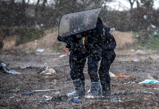 """French anti riot police officers protect themselves from a hailstorm, during the demolition of the southern part of the so-called """"Jungle"""" migrant camp, on March 2, 2016, in Calais. French demolition workers set about razing makeshift shelters in the """"Jungle"""" migrant camp for a third day on March 2, 2016 under close watch of dozens of police officers equipped with water cannon. (Photo by Philippe Huguen/AFP Photo)"""