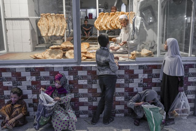 A child (C) buys bread as some children wait for free bread in front of a bakery in Kabul on September 14, 2021. (Photo by Bulent Kilic/AFP Photo)