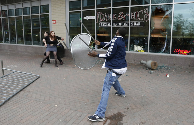 A protestor throws a chair at a restaurant near Oriole Park at Camden Yards as a woman tries to stop him after a rally for Freddie Gray, Saturday, April 25, 2015, in Baltimore. (Photo by Patrick Semansky/AP Photo)