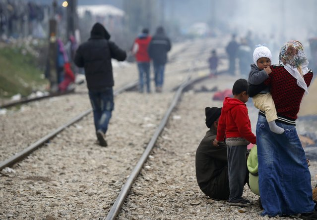 Migrants stand next to railway tracks at a makeshift camp on the Greek-Macedonian border near the village of Idomeni, Greece March 10, 2016. (Photo by Stoyan Nenov/Reuters)