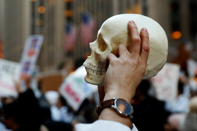 A demonstrator holds a skull aloft while taking part in a protest against a proposed repeal of the Affordable Care Act in New York, U.S., January 30, 2017. (Photo by Lucas Jackson/Reuters)