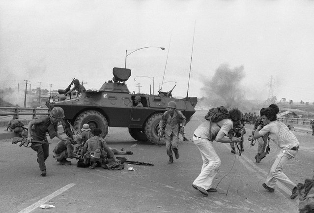 In this Monday, April 28, 1975 file photo, South Vietnamese troops and western TV newsmen run for cover as a North Vietnamese mortar round explodes on Newport Bridge on the outskirts of Saigon. (Photo by AP Photo/Hoanh)