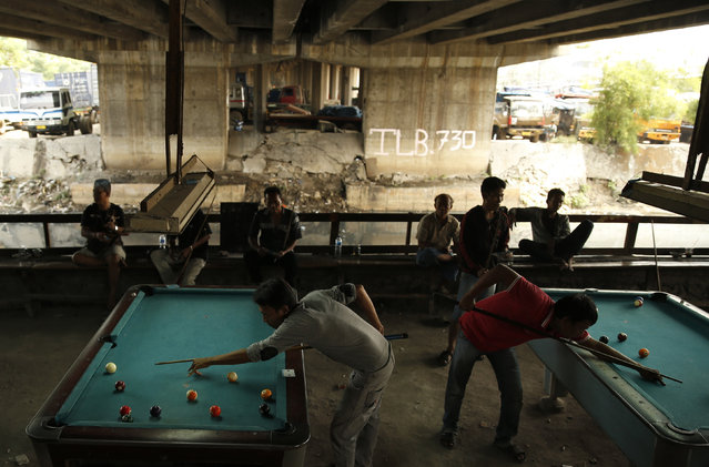 Indonesian public transport drivers play billiards under a highway toll road at a slum area in Jakarta, Indonesia, January 19, 2016. (Photo by Reuters/Beawiharta)