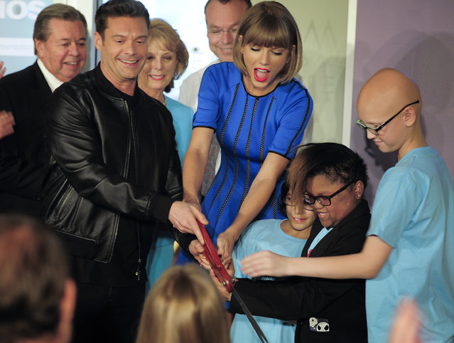 Television personality and producer Ryan Seacrest, foreground left, and singer Taylor Swift, center, join young patients at a ribbon cutting ceremony for the new Seacrest Studio, Friday, March 18, 2016, at Monroe Carell Jr. Children's Hospital at Vanderbilt in Nashville, Tenn. The fully functioning studio allows patients to record, do interviews, play songs and broadcast to the rooms in the hospital. (Photo by George Walker/The Tennessean via AP Photo)