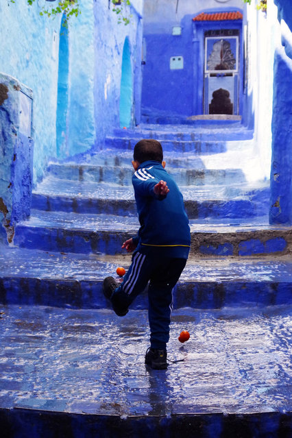 A boy in Chefchaouen, Morocco plays with oranges shot by Isabella Smith. (Photo by Isabella Smith/Travel Photographer of the Year)