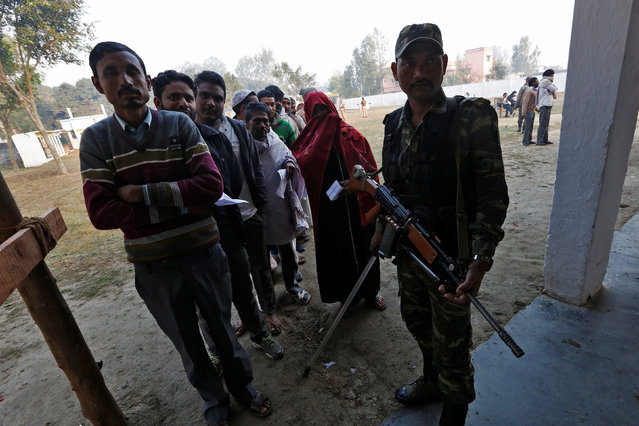 People queue to cast their vote as a security personnel stands guard at a polling station during the state assembly election in Hapur, in the central state of Uttar Pradesh, India, February 11, 2017. (Photo by Adnan Abidi/Reuters)