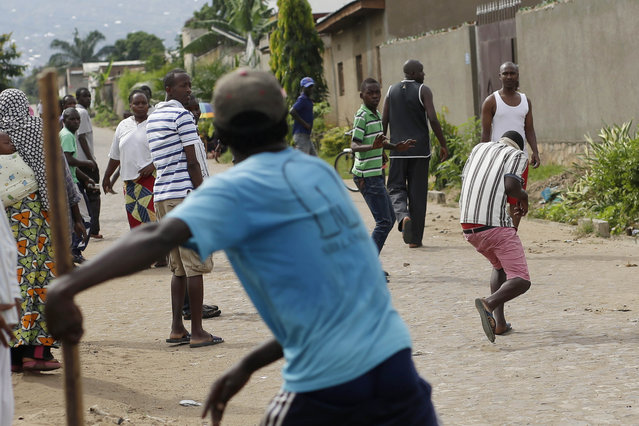 A suspected Imbonerakure militiaman runs away from demonstrators protesting President Pierre Nkurunziza's decision to seek a third term in office, throwing stones in the Cibitoke  district of Bujumbura, Burundi, Thursday May 7, 2015. (Photo by Jerome Delay/AP Photo)