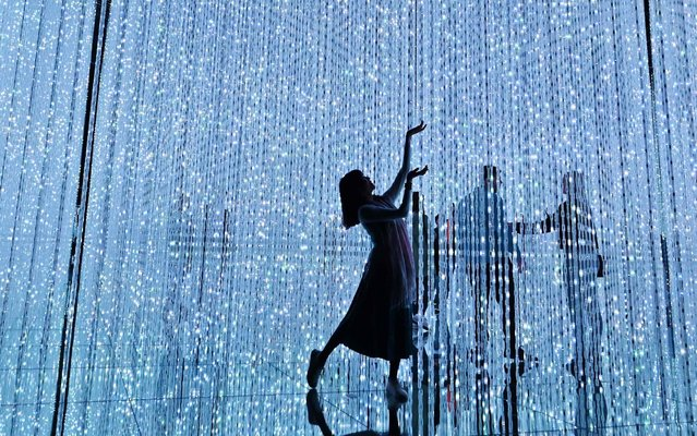 """This picture taken on April 28, 2019 shows a woman enjoying her visit at the team lab borderless museum of Tokyo. Collective teamLab, known internationally for their innovative """"digital art"""" that combines projections, sound and carefully designed spaces to create immersive experiences. (Photo by Charly Triballeau/AFP Photo)"""