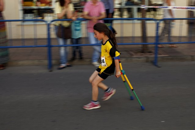 A girl running with crutches participates in a 3 kilometer (1.8 miles) race for children during the XVIII 101km international competition in Ronda, southern Spain, May 9, 2015. (Photo by Jon Nazca/Reuters)