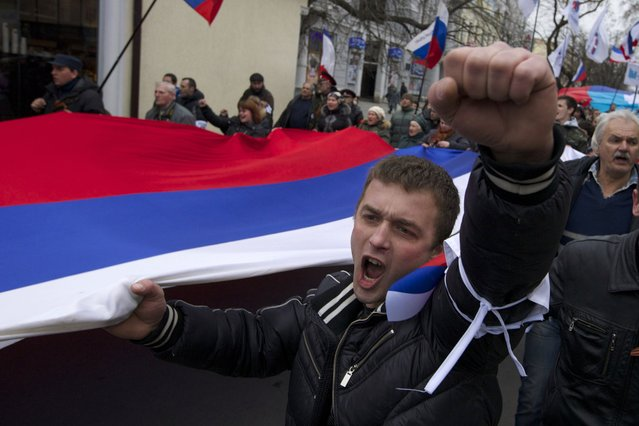 Local residents carry Russian flags and shout slogans rallying over the streets of Crimean capital Simferopol, Ukraine, on Saturday, March 1, 2014. Russian President Vladimir Putin asked parliament Saturday for permission to use the countryпїЅs military in Ukraine, moving to formalize what Ukrainian officials described as an ongoing deployment of Russian military on the countryпїЅs strategic region of Crimea. (Photo by Ivan Sekretarev/AP Photo)