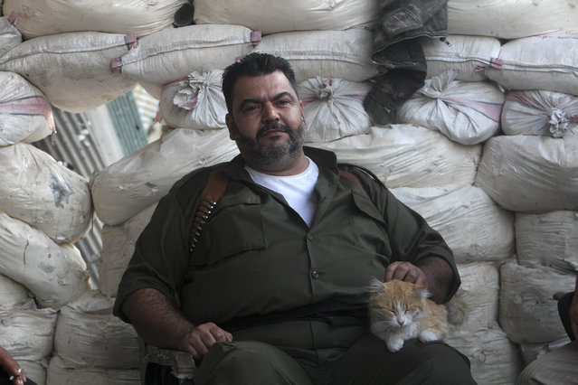 """A """"Free Syrian Army"""" fighter strokes a cat while sitting behind sandbags in Aleppo's Sheikh Saeed neighborhood, Syria September 28, 2013. (Photo by Muzaffar Salman/Reuters)"""