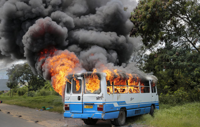 A bus burns after being set on fire by demonstrators in the Ngagara district of Bujumbura, Burundi Tuesday, May 12, 2015. A crowd who were marching to the funeral of a woman who died in recent protests were blocked from doing so by police, and the crowd then set fire to a bus and government car and motorcycle. (Photo by Berthier Mugiraneza/AP Photo)