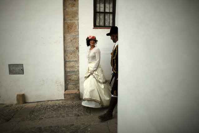 "A woman (L) dressed as a bourgeois and a man dressed as a bandit walk along an alley as they participate in the third edition of ""Ronda Romantica"" (Romantic Ronda) in Ronda, southern Spain, May 16, 2015. (Photo by Jon Nazca/Reuters)"