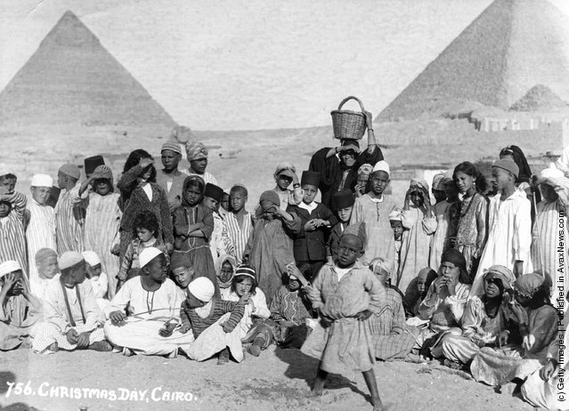 circa 1920: A group of Egyptian children pose in front of the ancient pyramids