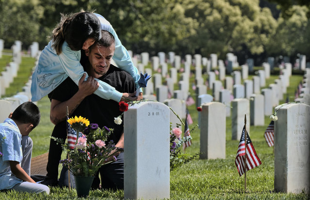 Carla Martinez comforts her cousin Ceaser Martinez as he weeps over his brother's grave on Memorial Day at the Veterans National Cemetery in Los Angeles on Monday, May 27, 2019. Rodrigo Matinez was killed in action in Iraq in 2004. (Photo by Richard Vogel/AP Photo)