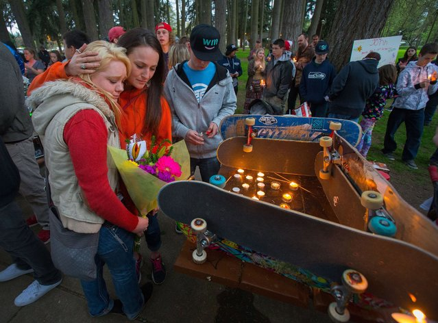 Sabreena Klepper, left, the girlfriend of John Mills, is comforted by friend Nicole Medford at a shrine built of skateboards during a memorial for Mills, who was shot and killed at Emerald Park the day before, Wednesday, April 13, 2016, in Eugene, Ore. The shooter, Orlando Centeno, also shot and wounded another man, then fled to a nearby residence where he killed himself with a self-inflicted gunshot. (Photo by Brian Davies/The Register-Guard via AP Photo)