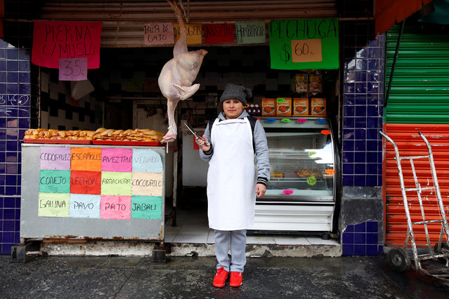 """Cristina Alvarez, 29, a butcher, poses for a photograph while standing outside her and her husband's butcher shop, in Mexico City, Mexico February 25, 2017. """"I've never felt any gender inequality"""", Alvarez said. """"I believe women can do the same jobs as men and that there should be no discrimination"""". (Photo by Jose Luis Gonzalez/Reuters)"""