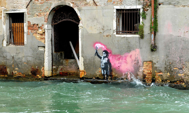 An alleged work by British street artist Banksy depicting a migrant child wearing a lifejacket holding a pink flare, is painted on the outer wall of a house overlooking the canal Rio de Ca Foscari, in Venice, on May 21, 2019. (Photo by Marco Sabadin/AFP Photo)