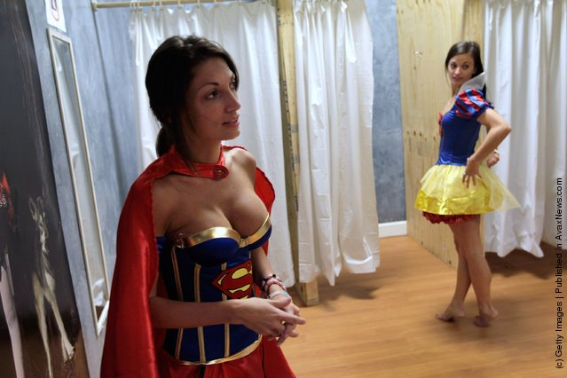 Gina Labianca (L) tries on a super woman outfit as Charlie Lucas tries a snow white Costume at the Halloween MegaStore