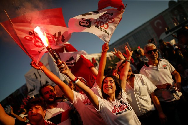 Supporters of Ekrem Imamoglu, the new Mayor of Istanbul from Turkey's main opposition opposition Republican People's Party (CHP) light a flare as he makes a speech after he took over office, in Istanbul, Thursday, June 27, 2019. Imamoglu is formally taking office as mayor of Istanbul four days after he won a repeat election in Turkey's largest city and commercial hub. (Photo by Emrah Gurel/AP Photo)