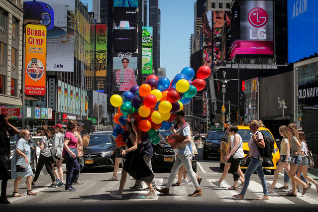 A woman carries a bunch of balloons through Times Square in New York, U.S., June 26, 2019. (Photo by Brendan McDermid/Reuters)