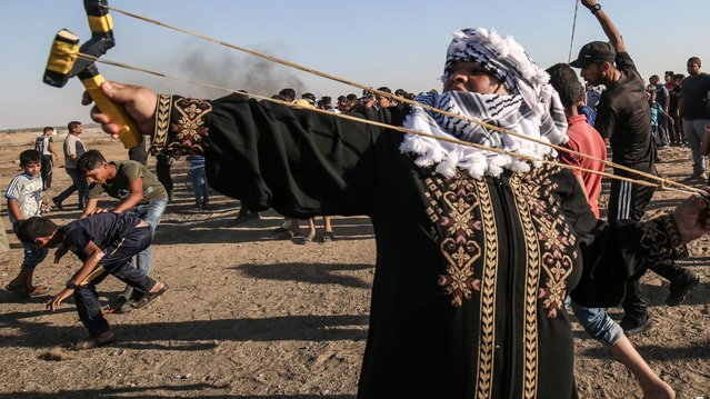 A Palestinian woman uses a slingshot to throw stones at Israeli forces across the border with Israel during protests along the border with Israel east of Khan Yunis in the southern Gaza strip on July 5, 2019. (Photo by Said Khatib/AFP Photo)