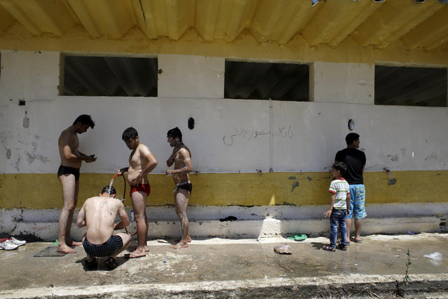 Migrants take a shower at a refugee and migrant camp in the village of Moria on the northeastern Greek island of Lesvos on Wednesday, June 17, 2015. The Aegean island has borne the brunt of a huge influx of migrants from the Middle East, Asia and Africa crossing from Turkey to nearby Greek islands. More than 50,000 migrants have arrived in Greece so far this year. (AP Photo/Thanassis Stavrakis)