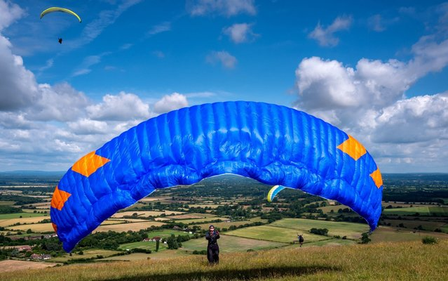 Paragliders taking advantage of the ideal flying conditions on the South Downs at Devil's Dyke, near Brighton on July 12, 2019 in Brighton, England. (Photo by Andrew Hasson/Getty Images)