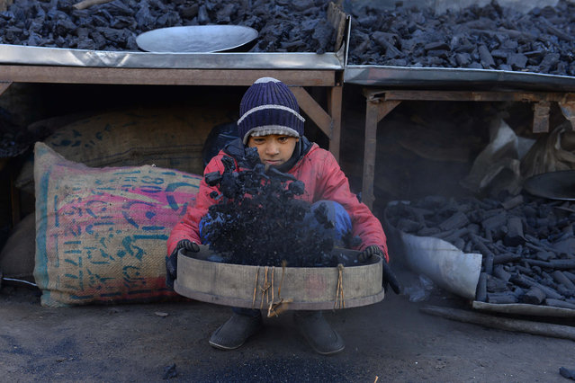 A young Afghan vendor sifts charcoal at his stall in Herat city on December 4, 2018. (Photo by Hoshang Hashimi/AFP Photo)