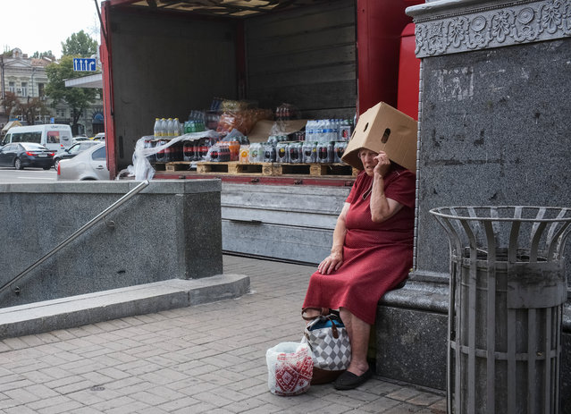An elderly woman covers her head from the sun as she begs for money in central Kiev, Ukraine on July 26, 2019. (Photo by Gleb Garanich/Reuters)