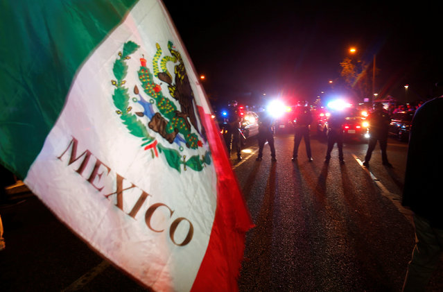 Police in riot gear form a line to break up a group of protesters, one with a Mexican flag, outside  Republican U.S. presidential candidate Donald Trump's campaign rally in Costa Mesa, California, April 28, 2016. (Photo by Mike Blake/Reuters)