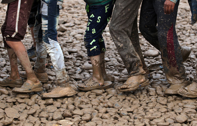 Iraqis, displaced from Mosul, walk around the muddy grounds of the Hammam al- Alil camp for the internally displaced, south of Mosul, on March 16, 2017, during an offensive by security forces to retake the western parts of the city from Islamic State (IS) group fighters. (Photo by Ahmad al-Rubaye/AFP Photo)