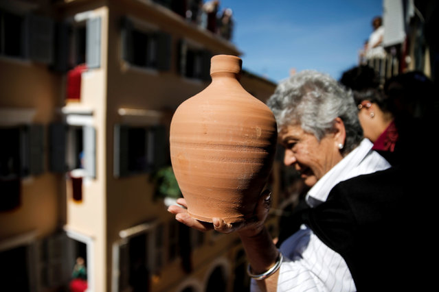 "A woman prepares to throw a clay pot from a balcony during the Greek Orthodox Easter tradition of ""Botides"" on Holy Saturday marking the so-called ""First Resurrection"", on the island of Corfu, Greece, April 30, 2016. (Photo by Alkis Konstantinidis/Reuters)"