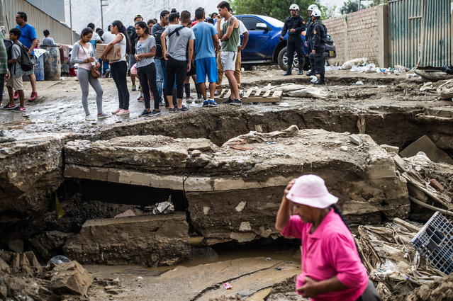 Local residents stand on a road damanged by the flash floods in Huachipa district, east of Lima, on March 19, 2017. (Photo by Ernesto Benavides/AFP Photo)