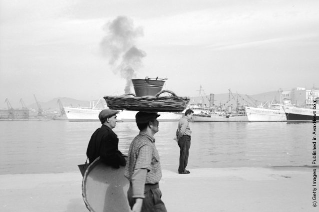 1947: A man balancing a large basket and a pail on his head walks along the harbour at Piraeus in Greece