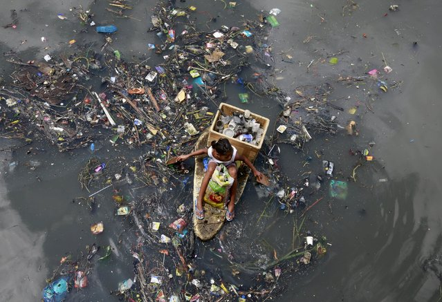 A girl sits on a makeshift styrofoam raft as she collects recyclable material from floating garbage in a polluted river at Navotas city, north of Manila, July 2, 2015. (Photo by Romeo Ranoco/Reuters)