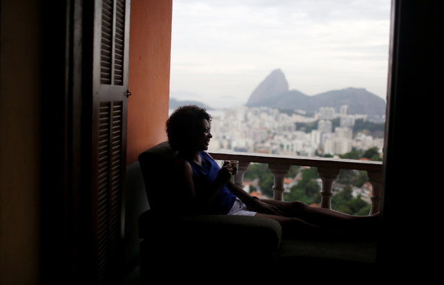 A guest relaxes with the The Sugar Loaf mountain in the background at Pousada Favelinha (Little favela) hostel in Pereira da Silva favela, in Rio de Janeiro, Brazil, April 29, 2016. (Photo by Pilar Olivares/Reuters)