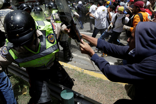 Demonstrators clash with security forces during an opposition rally in Caracas, Venezuela on April 4, 2017. (Photo by Marco Bello/Reuters)