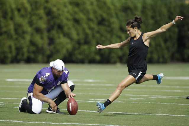 Baltimore Ravens' Sam Koch holds the ball for United States soccer player Carli Lloyd as she attempts to kick a field goal after the Philadelphia Eagles and the Baltimore Ravens held a joint NFL football practice in Philadelphia, Tuesday, August 20, 2019. (Photo by Matt Rourke/AP Photo)