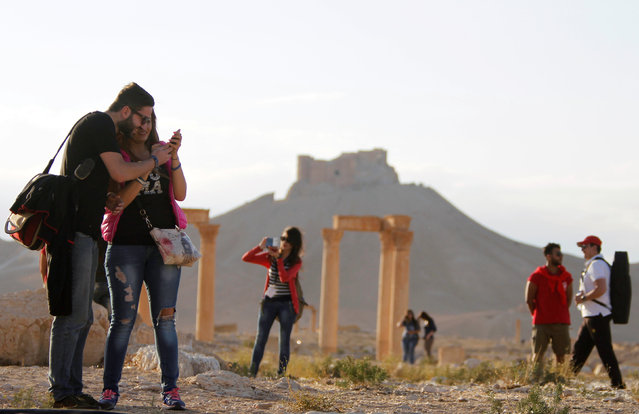 People visit the ruins of the historic city of Palmyra ahead of a musical event in its amphitheatre, as the Fakhreddin's Castle is seen in the background, Syria May 6, 2016. (Photo by Omar Sanadiki/Reuters)